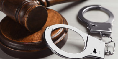 Judge's gavel and handcuffs on white wooden background, closeup. Criminal law concept